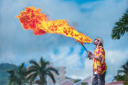photo people man blowing gas to make fire tree free for commercial use images