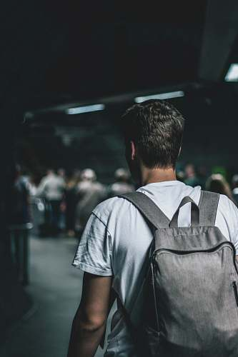 person man carrying backpack standing people