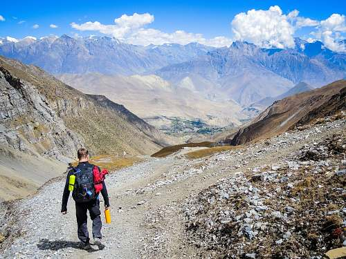 people man carrying backpack walking on mountain at daytime person