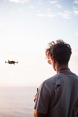 people man controlling drone at daytime person