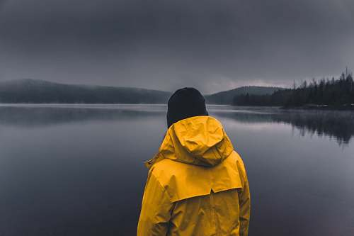 people man facing calm body of water under cloudy sky person