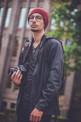 people man holding black DSLR camera person