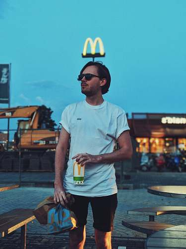 people man holding McDonald cup beside camping table person