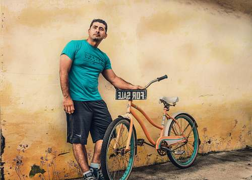bicycle man holding orange beach cruiser bike