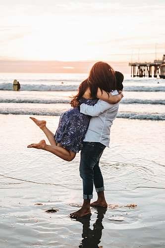 people man hugging woman on seashore person