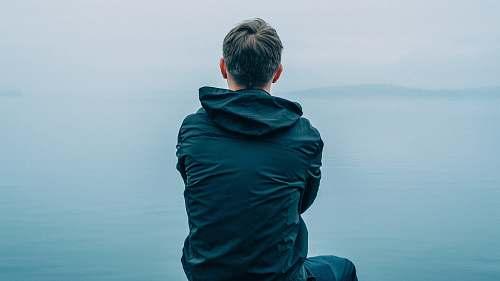 people man in black hoodie sitting in front of ocean person