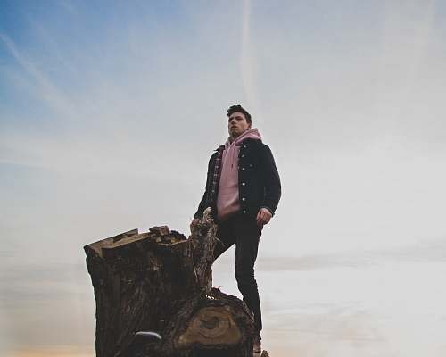 people man in black jacket and pink pullover hoodie standing on tree log person