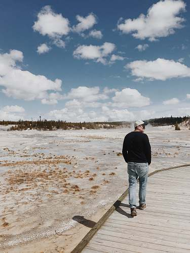 people man in black sweatshirt and blue denim jeans walking on wooden pathway under blue and white skies during daytie person