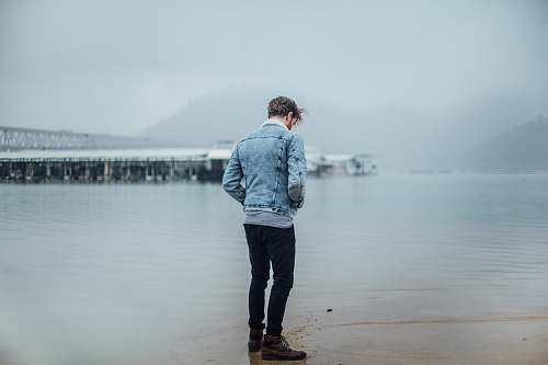 people man in blue denim jacket standing on shore person