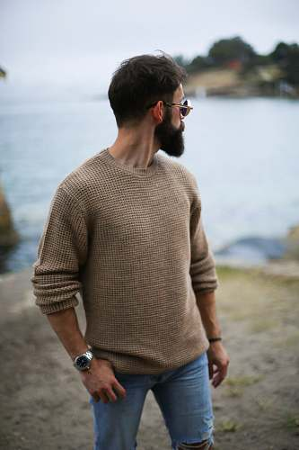 people man in brown knitted sweater near beach person