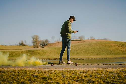 people man in green jacket and blue jeans on skateboard person
