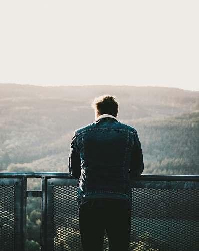 people man in green jacket looking at horizon during daytime person