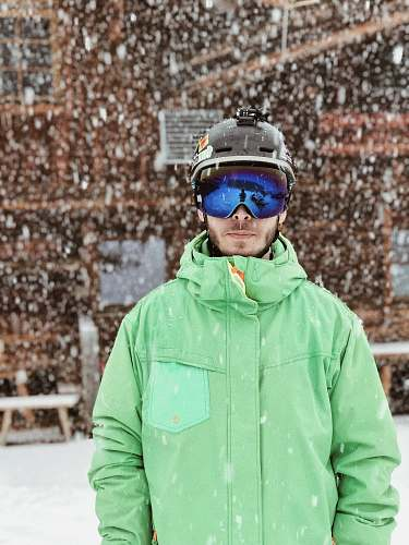 people man in green zip-up hooded jacket black helmet and black goggles standing on snow during daytime person
