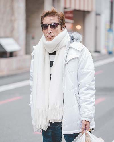 people man in white parka jacket and white scarf walking on street at daytime person