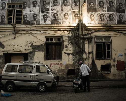 people man in white shirt beside black motor scooter looking up at sketch portraits hanged on building wall person