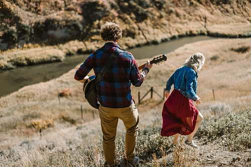 people man playing guitar standing behind woman on mountain person