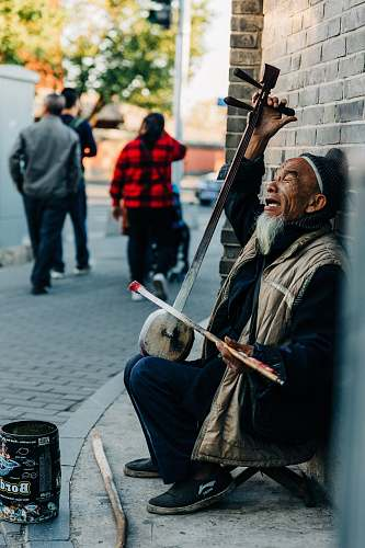 people man playing musical instrument on sidewalk person