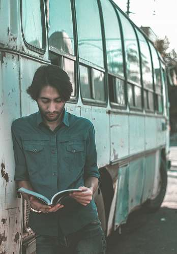 people man reading book while leaning on bus person