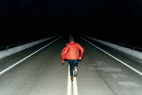 people man running on road during night time person