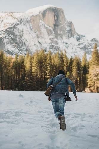 people man running on snow near snowy mountain during daytime person