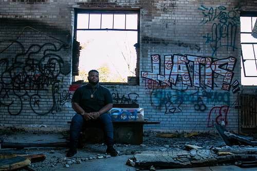 people man sitting on bench front of assorted-design graffiti on wall person