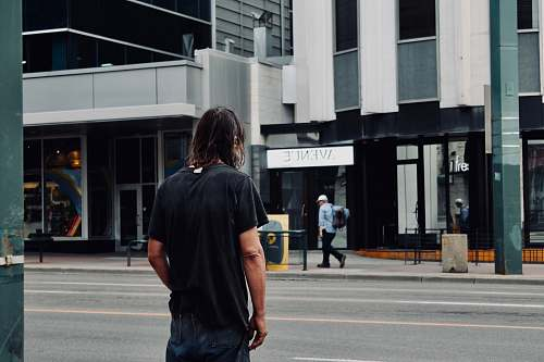 people man standing beside road near Avenue storefront person