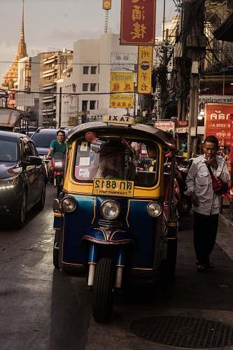 people man standing beside yellow auto rickshaw thailand