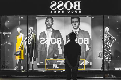 person man standing in front of Boss Hugo Boss store people