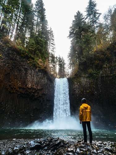 person man standing in front of water falls people