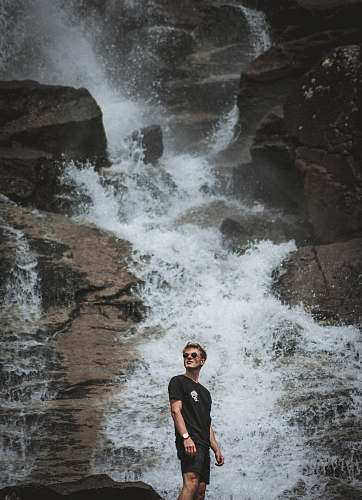 people man standing in front of waterfalls person