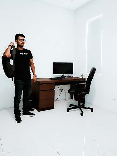 person man standing near brown desk beside white wall people