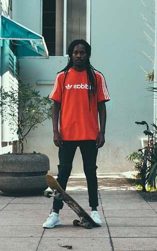 people man standing near gray garden pot with skateboard skateboard