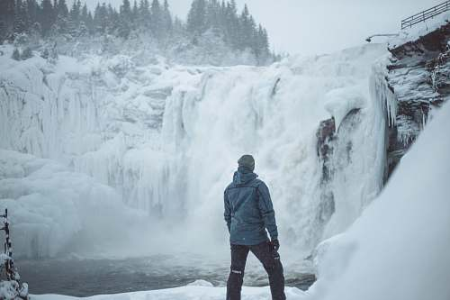 people man standing near snow covered falls during daytime person