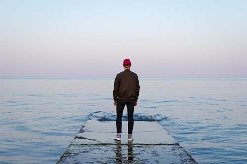 people man standing on concrete dock facing sea person