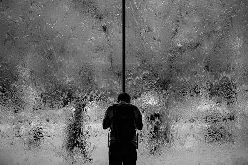 people man standing on glass wall with pouring water black-and-white