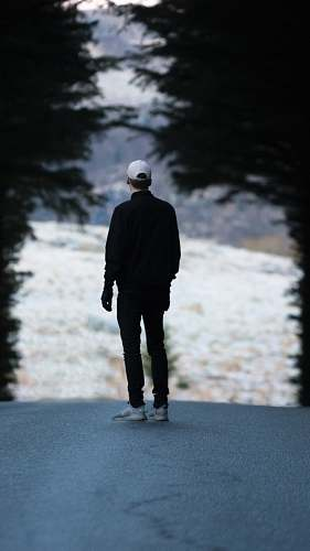 people man standing on pathway with trees person