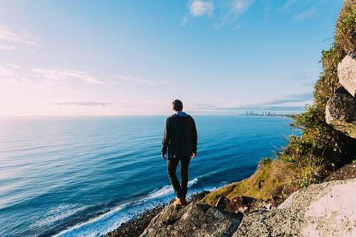 people man standing on rock cliff near sea person