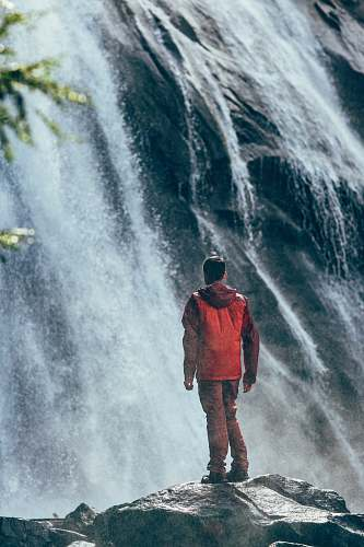 people man standing on rock facing waterfall nature