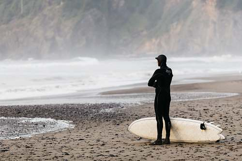 people man standing on shoreline with surfboard person