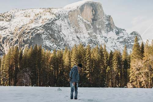 people man standing on snow field near trees and mountain during day person