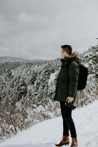 people man standing on snow looking at trees under cloudy sky person
