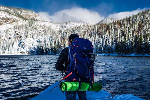 people man standing with blue hiking bag front of lake person