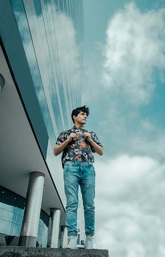people man walking beside glass building under cloudy blue sky during daytime person