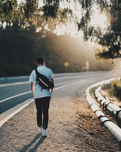 people man walking beside road during orange sunset person