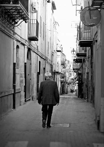 people man walking between of buildings black-and-white