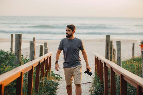 photo people man walking holding camera near shoreline person free for commercial use images