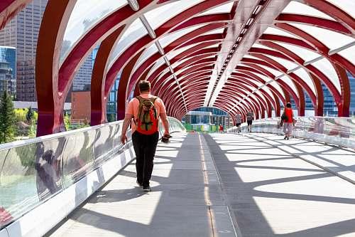 people man walking on arch bridge person