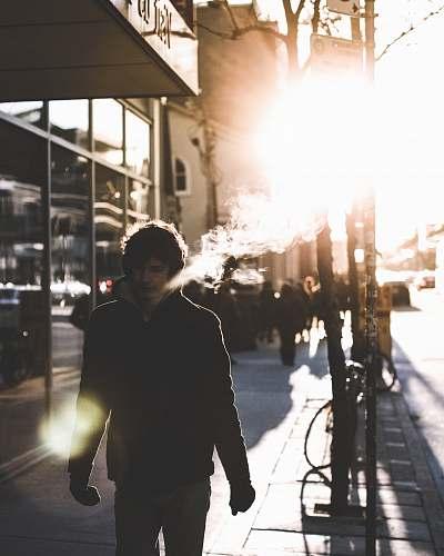 people man walking on sidewalk beside glass wall person
