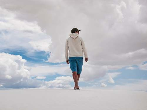 person man walking on white surface under white clouds and blue sky during daytime people