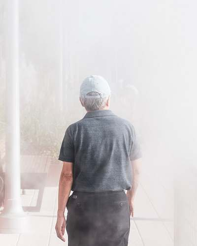 people man walking towards smoke-covered building person